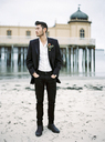 Young man wearing black suit on sandy beach - FOLF00571