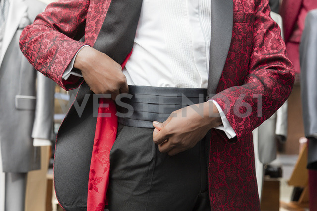 Mid section of a man dressing tuxedo in tailor shop - LFEF00107