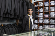 Elegant tailor standing in tailor shop glancing sideways - LFEF00110