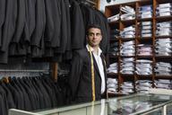 Elegant tailor standing in tailor shop glancing sideways - LFEF00110