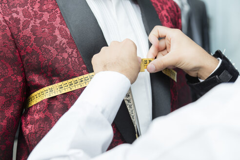 Detail of tailor measuring up client wearing tuxedo in tailor shop - LFEF00113