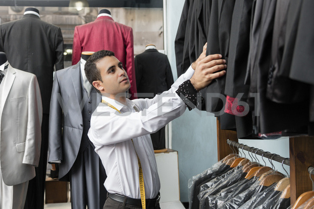Tailor tidying up suit jackets in tailor shop - LFEF00116