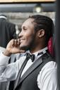 Smiling elegant man talking on phone in tailor shop - LFEF00122
