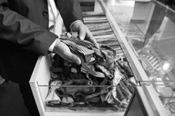 Tailor tidying up ties in glass case - LFEF00134