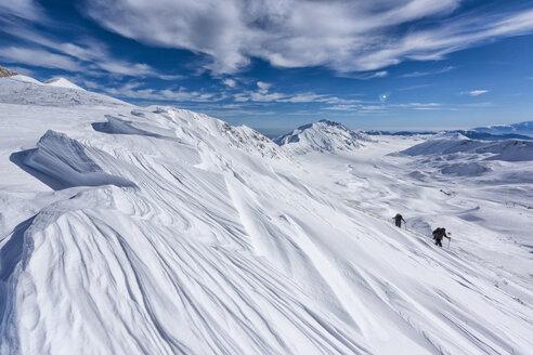 Italy, Abruzzo, Gran Sasso e Monti della Laga, Hikers on Campo Imperatore plateau in winter - LOMF00712
