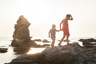 Girl walking with brother on coastal rocks - FOLF00732