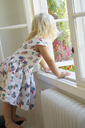 Young girl looking through window - FOLF00786