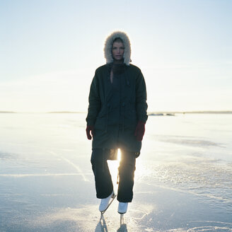 Mid adult woman in ice skates standing on frozen lake - FOLF00801