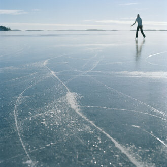 Mid adult woman ice skating on frozen lake - FOLF00804