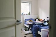 Boy sleeping on bed at home seen through doorway - CAVF28536