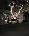 Athlete practicing on gymnastic rings at health club - CAVF28554