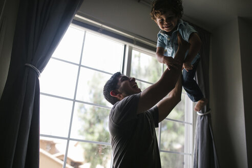 Happy father lifting son while standing by window at home - CAVF28560