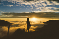 Silhouette woman standing on cliff against cloudscape during sunset - CAVF28611