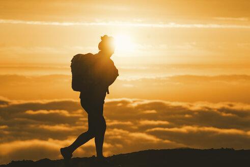 Silhouette female hiker walking on mountain during sunset - CAVF28632
