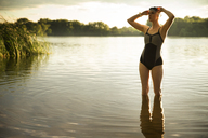 Thoughtful swimmer standing in lake - CAVF28683
