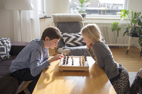 Boy and girl playing chess in living room - FOLF01108