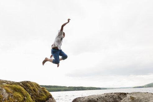 Teenage boy jumping from rocks - FOLF01177