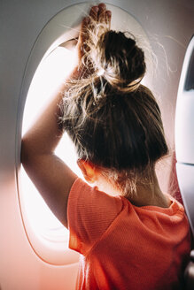 Rear view of girl looking through airplane window - CAVF28697