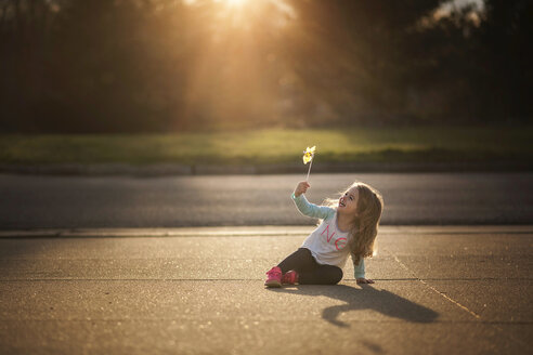 Cheerful girl playing with pinwheel toy while sitting on footpath during sunset - CAVF28745