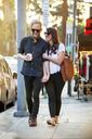 Happy couple walking on sidewalk - CAVF28748