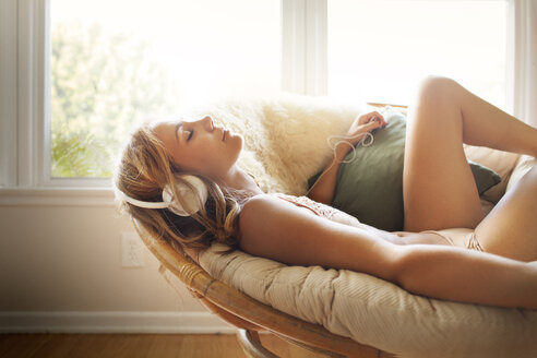 Relaxed woman listening music while lying on sofa at home - CAVF28751