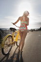 Rear view of woman in bodysuit walking with bicycle on street by beach - CAVF28754