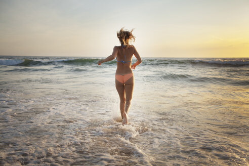 Rear view of woman running on beach during sunset - CAVF28769
