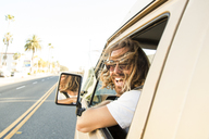 Portrait of cheerful man in mini van on road - CAVF28805