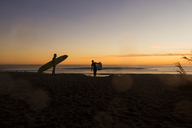 Couple carrying surfboards while walking on San Onofre State Beach during sunset - CAVF28823