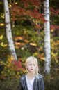 Portrait of blonde girl with autumn trees in background - FOLF01343