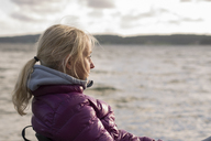 Portrait of blonde mature woman sitting at seaside - FOLF01346