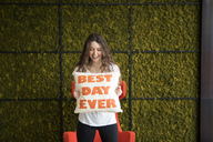 Happy young woman holding cushion with best day ever text while standing against wall at home - CAVF28886