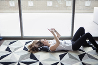 Young woman using smart phone while lying on carpet by window at home - CAVF28889