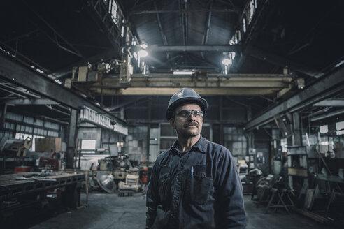 Male worker looking away while standing in metal industry - CAVF28964