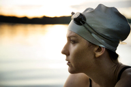 Close-up of thoughtful female swimmer sitting by lake - CAVF29142