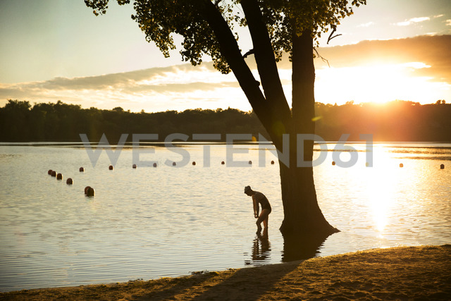 Female swimmer exercising in lake during sunset - CAVF29145