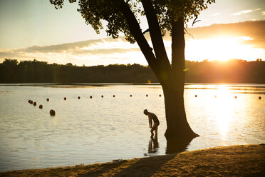 Female swimmer exercising in lake during sunset - CAVF29145