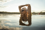 Female swimmer stretching arms in lake against sky - CAVF29151
