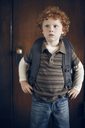 Curious boy carrying backpack while standing against door - CAVF29187