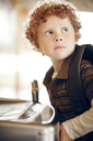 Close-up of boy standing near drinking fountain at school - CAVF29190