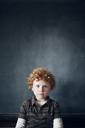 Portrait of boy standing in front of blackboard at school - CAVF29193