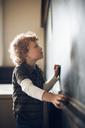 Side view of schoolboy drawing on blackboard - CAVF29196