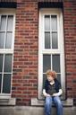Boy sitting against window of school building - CAVF29199