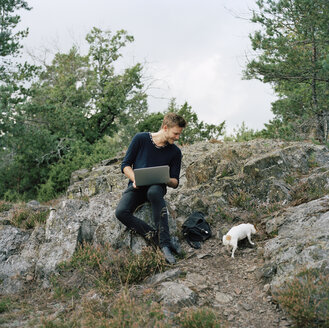 Man with laptop looking at dog in forest - FOLF01577