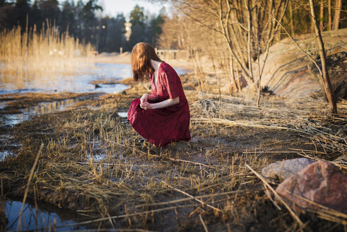Young woman crouching in wetlands - FOLF01643