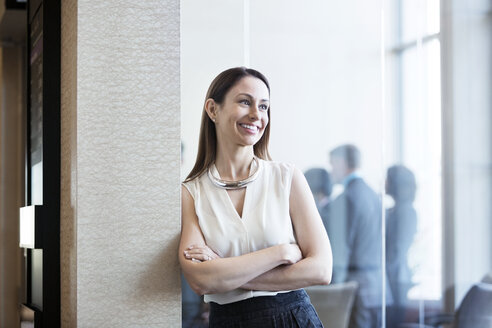 Happy businesswoman leaning on wall in office - CAVF29347