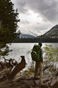 Hiker carrying backpack while standing on driftwood by river at Yosemite National Park - CAVF29362