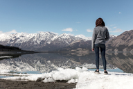 Full length of woman standing on snow by river while looking at view against mountains and sky - CAVF29422