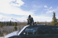 Woman looking at view while sitting on car roof at Denali National Park - CAVF29425