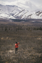 Rear view of woman standing on field against snowcapped mountains at Denali National Park - CAVF29428
